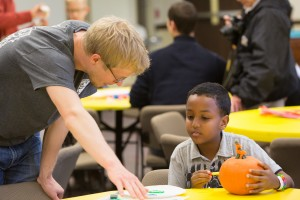 Seminary student Paul Flo, left, helps a child decorate a pumpkin in the Kids' Corner as part of the 175th anniversary celebration.