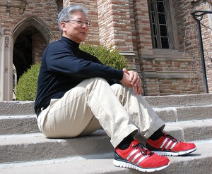 Dr. Joel Okamoto sports his trademark red sneakers on the steps outside of Luther Tower.