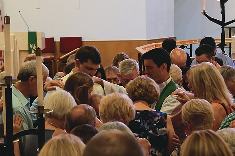 Rev. Steve Carretto, center, leads his congregation in prayer for Vicar Jacob and Rebecca Schultz and their son, Isaiah, on their last Sunday at St. Paul Lutheran Church.